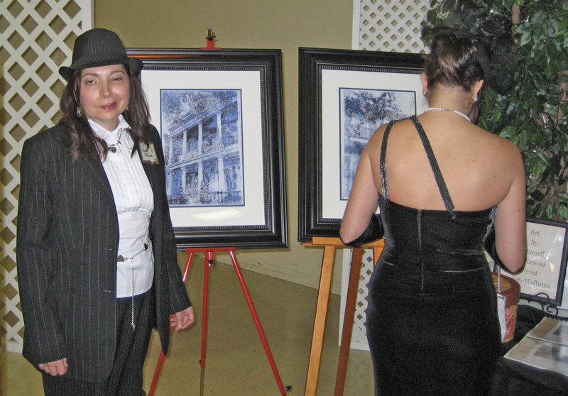 Artist Susan Talbot Hoffmann standing before the display of her donated prints to the Mad Hatter's anual fund raiser.